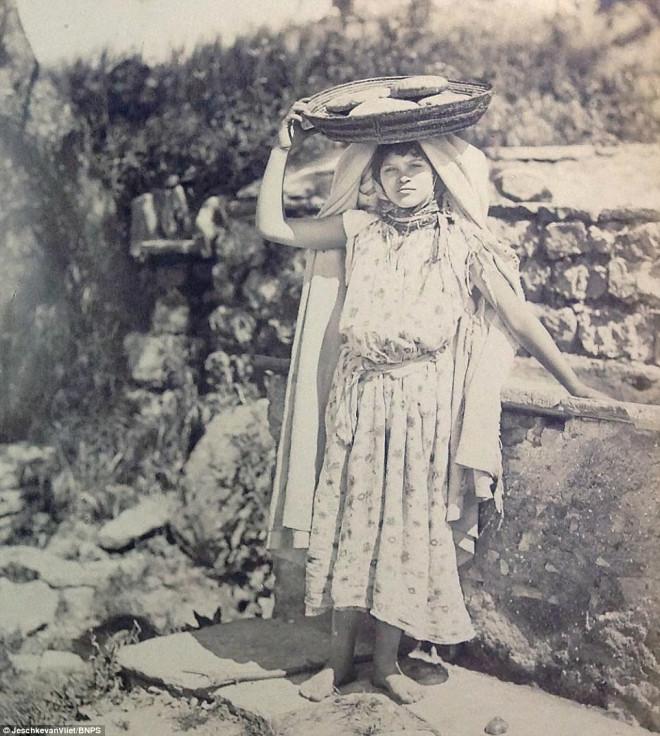 Başında bir sepet içinde ekmek taşıyan bir kadın...