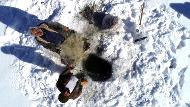 Buz kütlesini kırıp balık avlıyorlar!