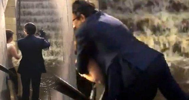 Takım elbiseli bir adam, selde ıslanmamak için çözümü kadının sırtına çıkarak buldu