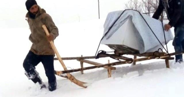 Kar yağışının esir aldığı kentte, arızalı bulaşık makinesi kızakla taşındı