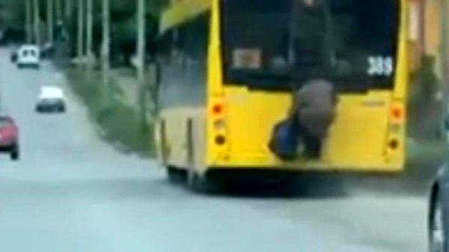 Yaşlı kadın, toplu taşıma sınırlamasına aracın arkasına tutunup yolculuk ederek meydan okudu