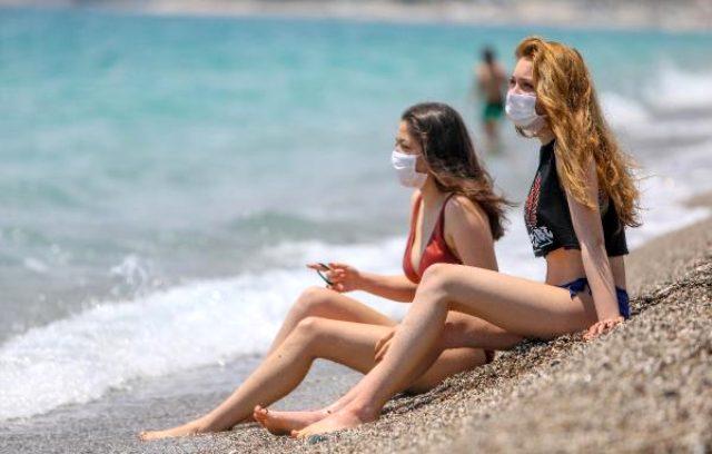 Tatilciler, Akdeniz kıyısında maske takarak güneşlendi