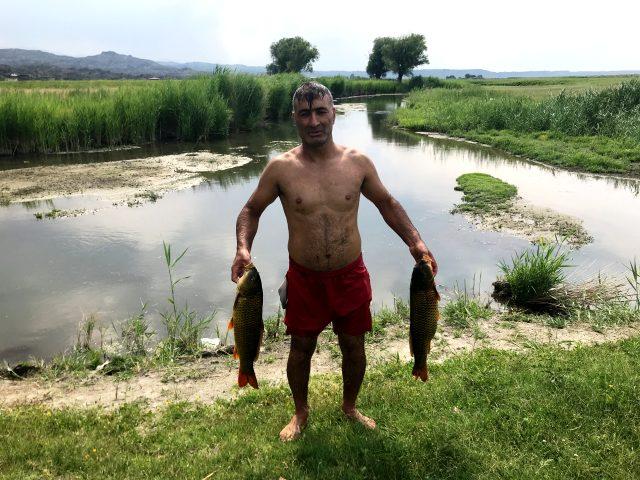 Olta ile balık tutmanın mümkün olmadığı çayda elle balık tutan adam