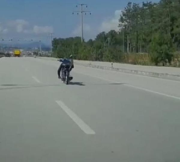 MUĞLA Üzerine uzandığı motosikleti tek eliyle kullanan sürücü yürekleri ağza getirdi