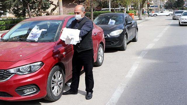 Sürücülerin araç içindeki çöplerini dışarıya atmaması için bastırdığı 20 bin poşeti trafikte dağıtıyor