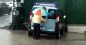 Bir elinde fırça, bir elinde şemsiye yağmur altında arabasını yıkadı