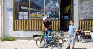 Aldığı emanet eşyalarla dükkanı dolduğu için bisiklet tamirini sokakta yapıyor